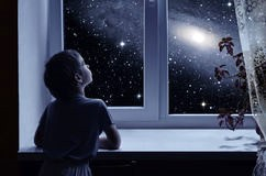 kid staring out a window looking at a galaxy in the night sky